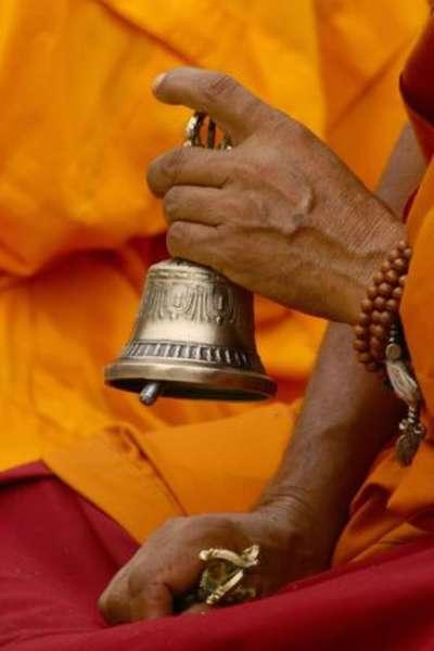 монах держит колокольчик
